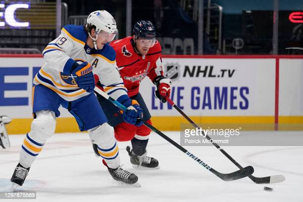 Jake McCabe of the Buffalo Sabres controls the puck against Daniel Sprong of the Washington Capitals in the first period at Capital One Arena on...