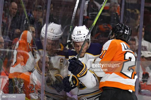 Jake McCabe of the Buffalo Sabres is checked by Scott Laughton of the Philadelphia Flyers during the second period at Wells Fargo Center on December...