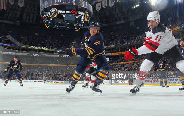 Jake McCabe of the Buffalo Sabres skates with Brian Boyle of the New Jersey Devils during the second period of an NHL game on January 30 2018 at...