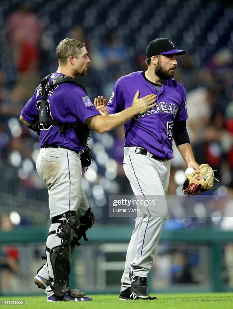 Jake McGee #51 of the Colorado Rockies is congratulated by Tom Murphy #23 after finishing the game in the ninth inning against the Philadelphia Phillies at Citizens Bank Park on June 13, 2018 in Philadelphia, Pennsylvania. The Rockies won 7-2.