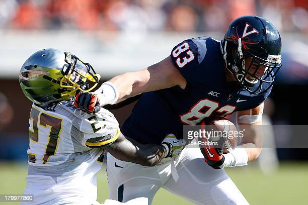 Jake McGee of the Virginia Cavaliers fights for extra yardage after a reception against Terrance Mitchell of the Oregon Ducks during the game at...