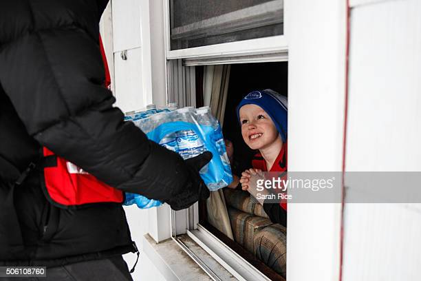 Jake McSigue of Linden receives a packahe of bottled water through the window of his grandma's home January 21 2016 in Flint Michigan McSigue was...