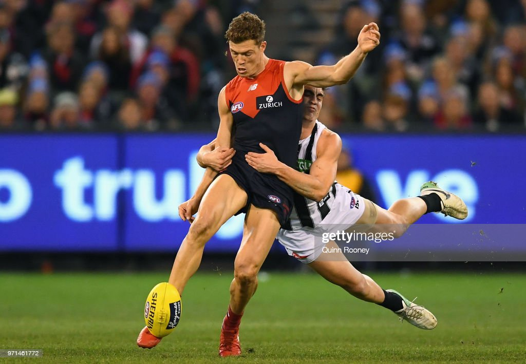 Jake Melksham of the Demons kicks whilst being tackled by Brayden Maynard of the Magpies during the round 12 AFL match between the Melbourne Demons and the Collingwood Magpies at Melbourne Cricket Ground on June 11, 2018 in Melbourne, Australia.