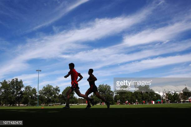 Jake Melksham of the Demons runs laps with an athlete hires as a pacemaker during a Melbourne Demons AFL training session at Gosch's Paddock on...