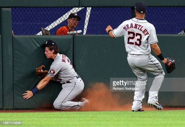 Jake Meyers of the Houston Astros hits the wall after making a catch on a fly ball hit by DJ Peters of the Texas Rangers in the third inning at Globe...