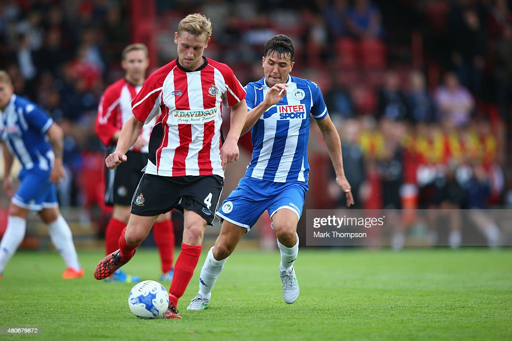 Jake Moult of Altrincham tangles with Tim Chow of Wigan Athletic during the pre season friendly between Altrincham and Wigan Athletic at the J Davidson stadium on July 14, 2015 in Altrincham, England.