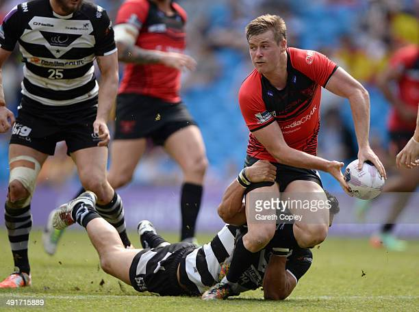 Jake Mullaney of Salford Red Devils is tackled by Magraff Leuluai of Widnes Vikings during the Super League match between Widnes Vikings and Salford...