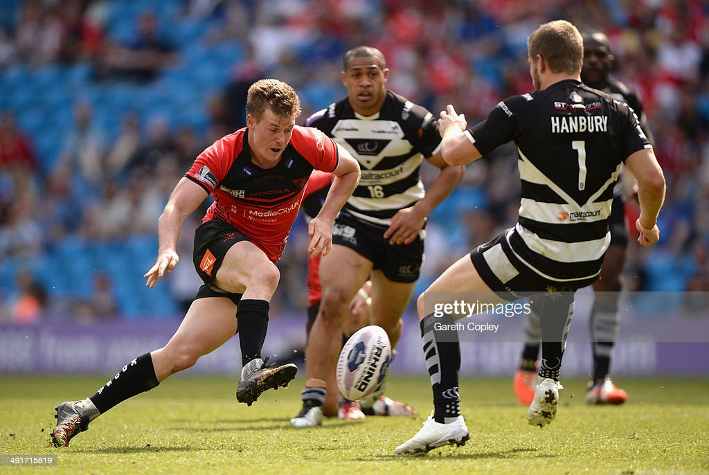 Jake Mullaney of Salford Red Devils kicks past Rhys Hanbury of Widnes Vikings during the Super League match between Widnes Vikings and Salford Red Devils at Etihad Stadium on May 17, 2014 in Manchester, England.