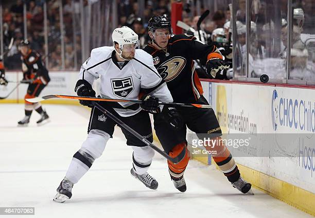Jake Muzzin of the Los Angeles Kings checks Corey Perry of the Anaheim Ducks into the boards while pursuing the puck in the first period at Honda...