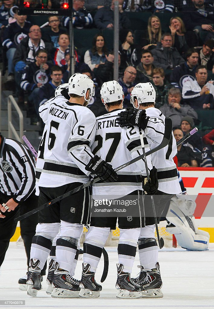 Jake Muzzin #6, Alec Martinez #27 and Tyler Toffoli #73 of the Los Angeles Kings celebrate a third period goal against the Winnipeg Jets at the MTS Centre on March 6, 2014 in Winnipeg, Manitoba, Canada.