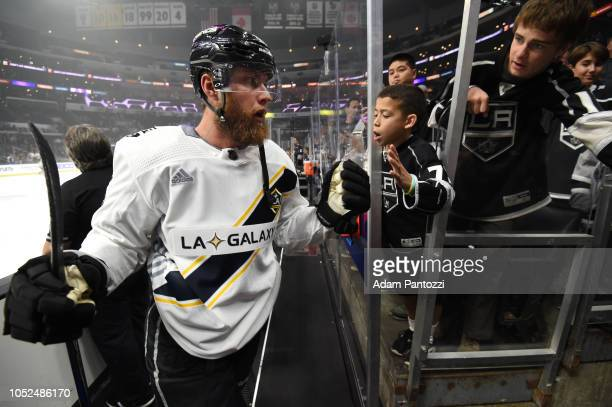 Jake Muzzin of the Los Angeles Kings and young fans highfive as Muzzin leaves the ice before the game against the New York Islanders at STAPLES...