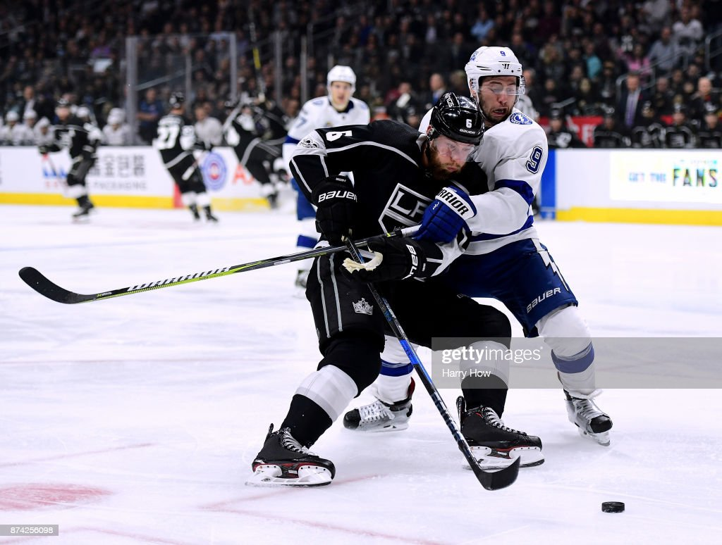 Jake Muzzin #6 of the Los Angeles Kings attempts a shot around Tyler Johnson #9 during the second period at Staples Center on November 9, 2017 in Los Angeles, California.