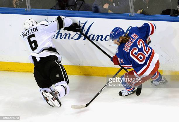 Jake Muzzin of the Los Angeles Kings hits the wall in front of Carl Hagelin of the New York Rangers in the first period of Game Four of the 2014...
