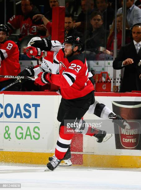 Jake Muzzin of the Los Angeles Kings is checked near the boards by Stefan Noesen of the New Jersey Devils during the game at Prudential Center on...