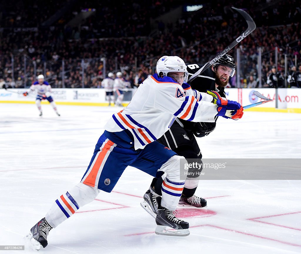 Jake Muzzin #6 of the Los Angeles Kings slows Taylor Hall #4 of the Edmonton Oilers to the puck during the third period at Staples Center on November 14, 2015 in Los Angeles, California.