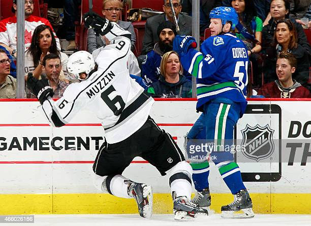 Jake Muzzin of the Los Angeles Kings stumbles after colliding with Derek Dorsett of the Vancouver Canucks during their NHL game at Rogers Arena March...