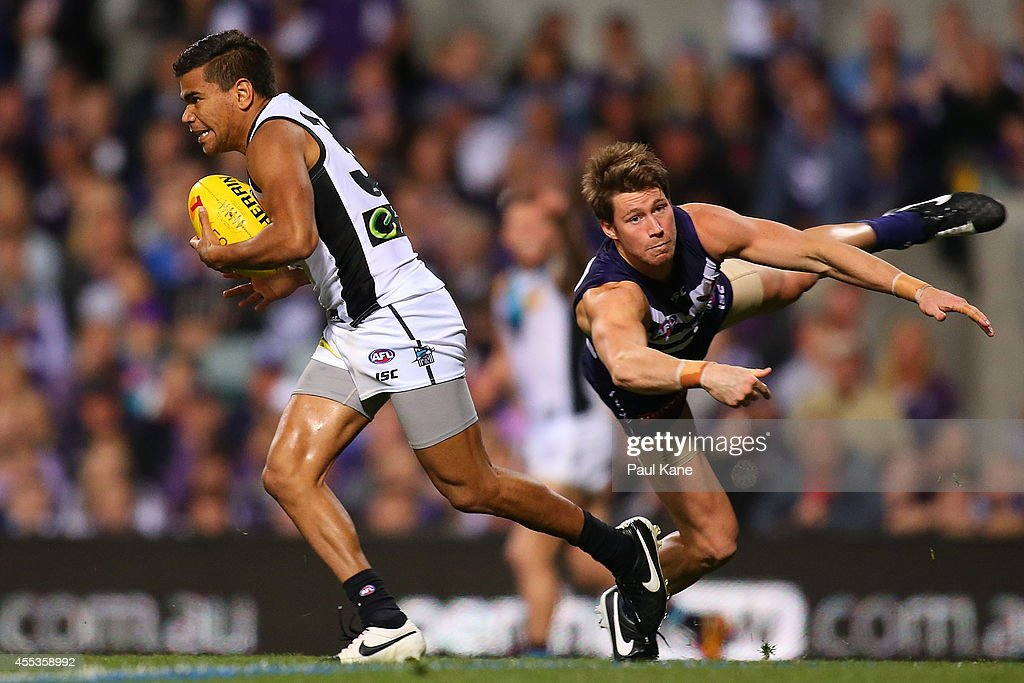 Jake Neade of the Power breaks from a tackle by Lee Spurr of the Dockers during the AFL 1st Semi Final match between the Fremantle Dockers and the Port Adelaide Power at Patersons Stadium on September 13, 2014 in Perth, Australia.