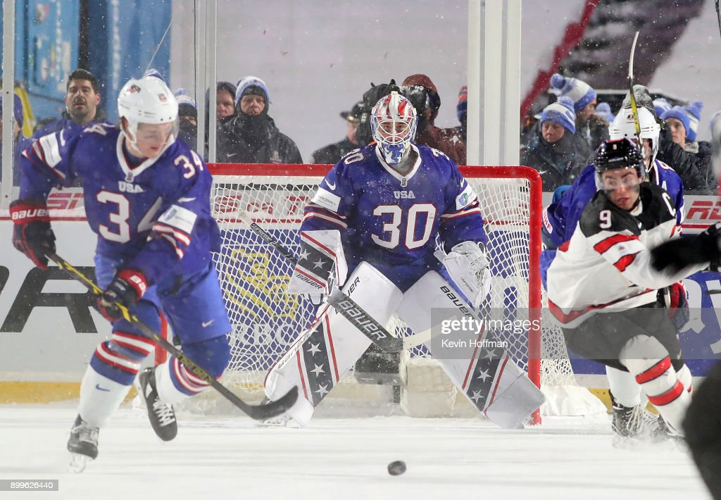 Jake Oettinger #30 of United States tends net as Trent Frederic #34 and Dillon Dube #9 of Canada go after a puck during the IIHF World Junior Championship at New Era Field on December 29, 2017 in Buffalo, New York. The United States beat Canada 4-3.