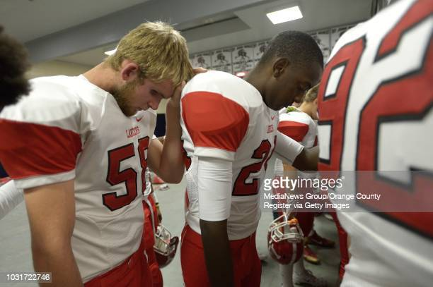 Jake Olson the long snapper for Orange Lutheran High left prays with his team including Kendall Hollowell center before their game against St John...