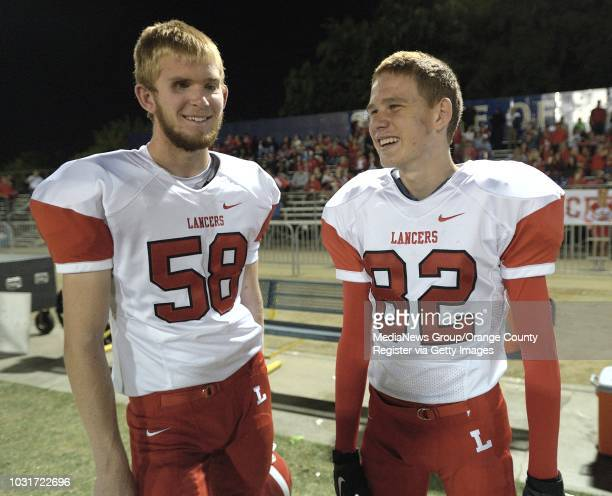 Jake Olson the long snapper for Orange Lutheran High right chats with teammate Walter Funk on the sidelines of a game against St John Bosco in...