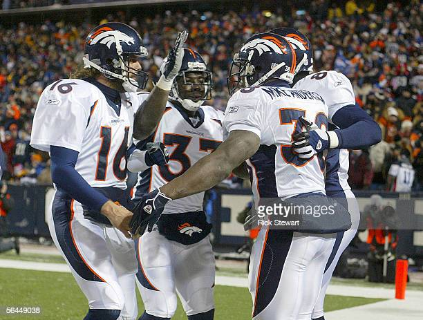 Jake Plummer Cecil Sapp and Rod Smith of the Denver Broncos congratulate teammate Mike Anderson after he scored his first of two touchdowns against...