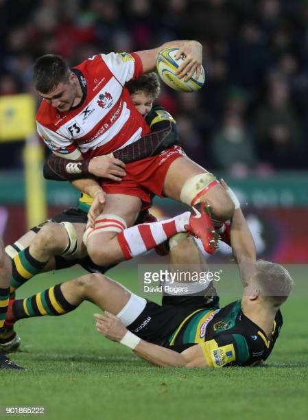 Jake Polledri of Gloucester is tackled by Jamie Gibson and Harry Mallinder during the Aviva Premiership match between Northampton Saints and...