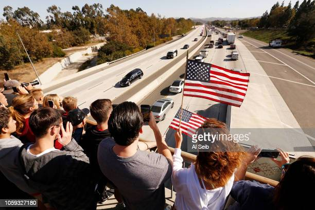 Jake Poppen with his Mother Joell Poppen hold flags as they watch the flag draped casket pass in a procession for Ventura County Sheriff's Sgt Ron...