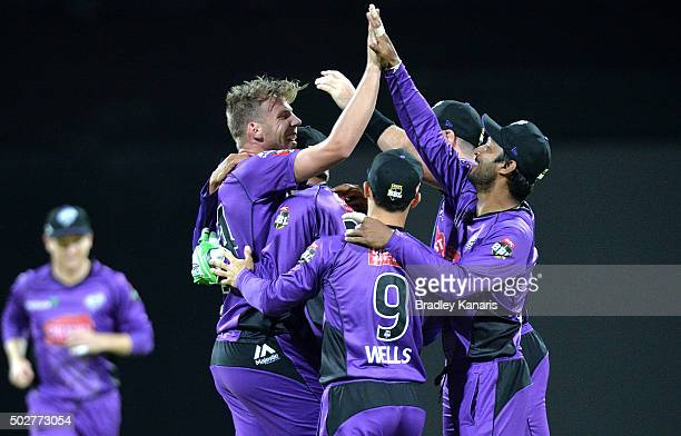 Jake Reed of the Hurricanes celebrates with team mates after taking the wicket of Jimmy Peirson of the Heat during the Big Bash League match between...