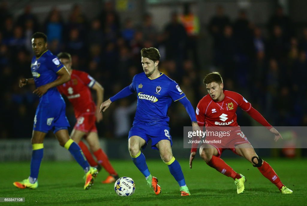 Jake Reeves of A.F.C. Wimbledon is closely watched by Harvey Barnes of Milton Keynes Dons during the Sky Bet League One match between A.F.C. Wimbledon and Milton Keynes Dons at The Cherry Red Records Stadium on March 14, 2017 in Kingston upon Thames, England.