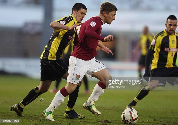 Jake Robinson of Northampton Town attempts to move away with the ball from Anthony O'Connor of Burton Albion during the npower League Two match...