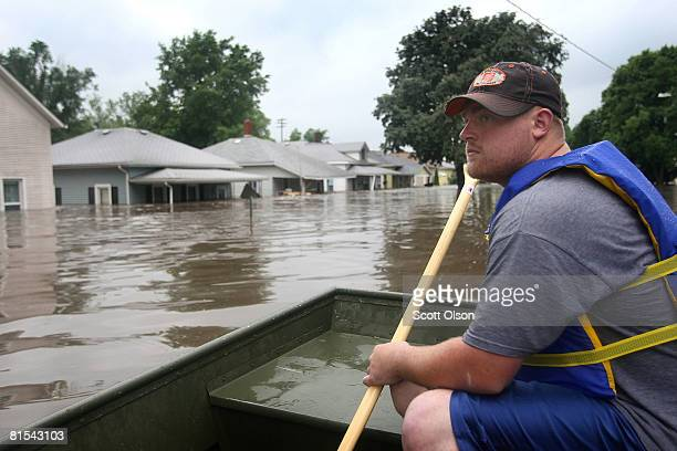 Jake Siggins of the Lisbon, Iowa Fire Department surveys homes searching for flood victims in need of rescue June 12, 2008 in Cedar Rapids, Iowa. The...