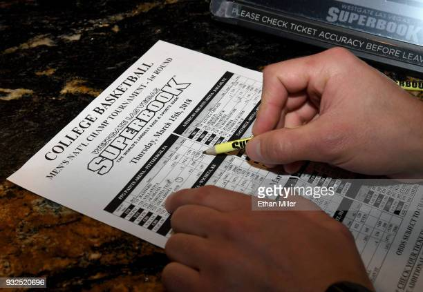 Jake Sindberg of Wisconsin makes bets during a viewing party for the NCAA Men's College Basketball Tournament inside the 25000squarefoot Race Sports...