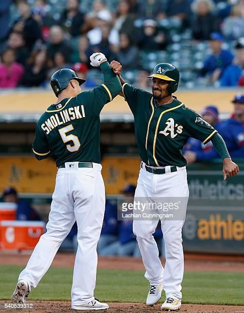 Jake Smolinski of the Oakland Athletics celebrates with Marcus Semien of the Oakland Athletics after they both scored on a Smolinski home run in the...