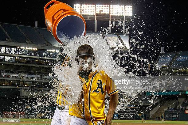 Jake Smolinski of the Oakland Athletics pours water on Billy Burns after he hit a walk off single against the Los Angeles Angels of Anaheim after the...