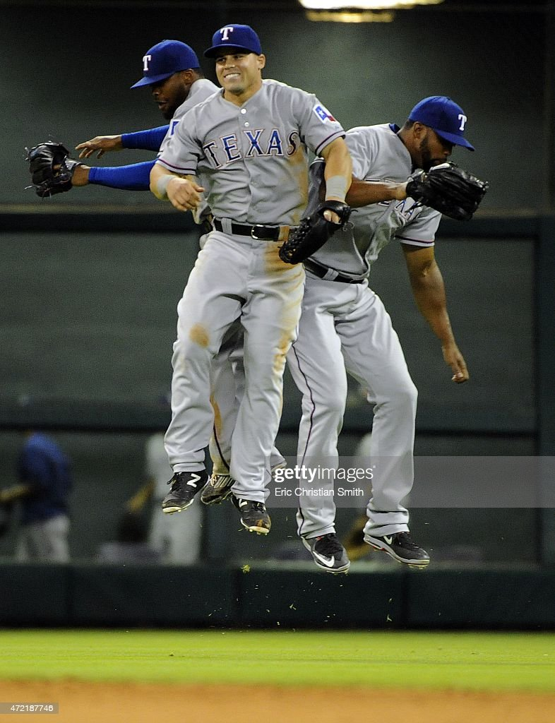 Jake Smolinski #20 of the Texas Rangers, center, Delino DeShields #7, left, and Carlos Peguero #43 celebrate the Rangers' 2-1 victory over the Houston Astros at Minute Maid Park on May 4, 2015 in Houston, Texas.
