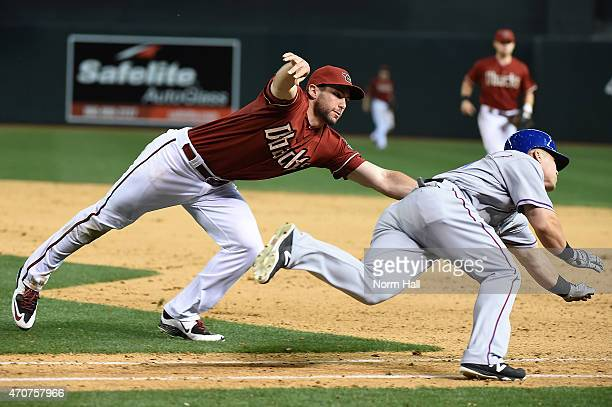 Jake Smolinski of the Texas Rangers is called out on a diving tag by Paul Goldschmidt of the Arizona Diamondbacks during the ninth inning at Chase...