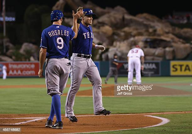 Jake Smolinski of the Texas Rangers is congratulated by Adam Rosales after hitting a tworun home run against the Los Angeles Angels of Anaheim in the...