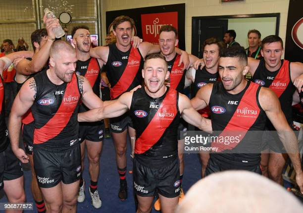 Jake Stringer Devon Smith and Adam Saad of the Bombers are sprayed with drinks as the Bombers sing the song in the rooms after winning the round one...