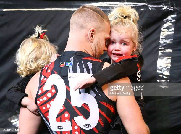 Jake Stringer of Essendon comes out with his kids for his 100th match during the round 11 AFL match between the Essendon Bombers and the Richmond...