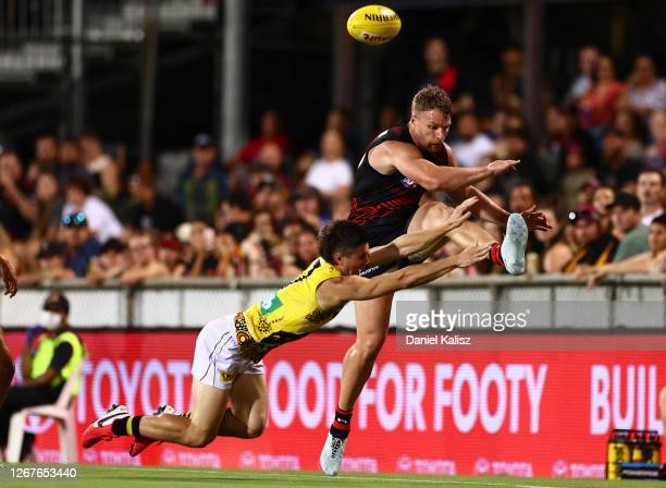 Jake Stringer of the Bombers has his kick smothered by Liam Baker of the Tigers during the round 13 AFL match between the Essendon Bombers and the...