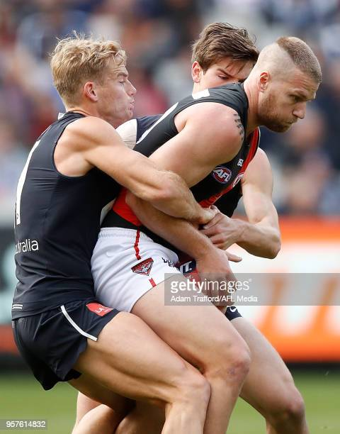 Jake Stringer of the Bombers is tackled by Sam Kerridge and Paddy Dow of the Blues during the 2018 AFL round eight match between the Carlton Blues...
