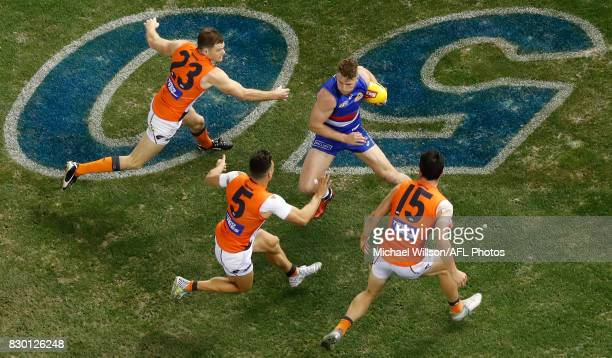 Jake Stringer of the Bulldogs is pressured by Heath Shaw Dylan Shiel and Matthew Kennedy of the Giants during the 2017 AFL round 21 match between the...