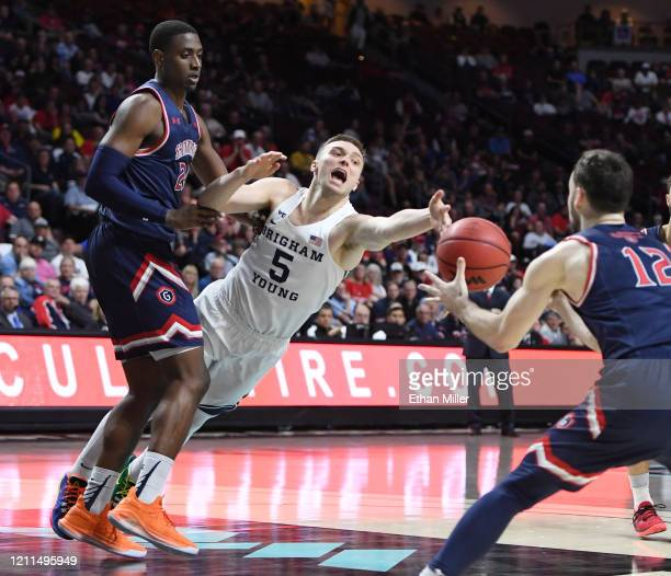 Jake Toolson of the Brigham Young Cougars loses the ball as he drives against Malik Fitts and Tommy Kuhse of the Saint Mary's Gaels during the West...