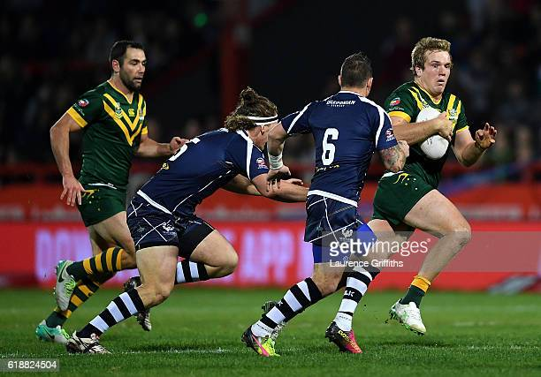 Jake Trbojevic of Australia breaks past Sheldon PoweHobbs and Danny Brough of Scotland during the Four Nations match between the Australian Kangaroos...