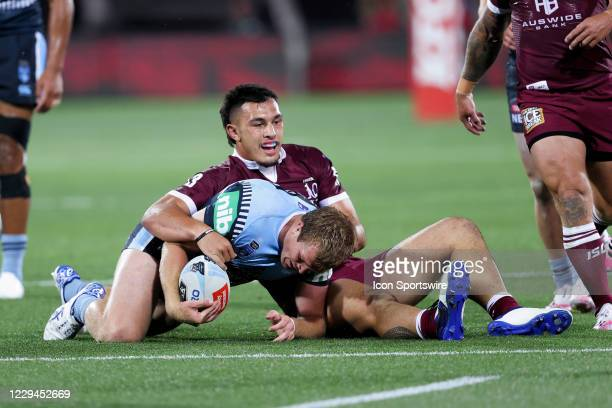 Jake Trbojevic of the NSW Blues tackled by Tino Faasuamaleaui of the QLD Maroons during game one of the 2020 State of Origin series between the...