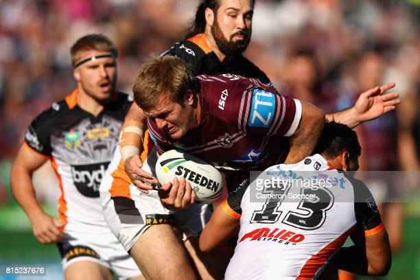 Jake Trbojevic of the Sea Eagles is tackled during the round 19 NRL match between the Manly Sea Eagles and the Wests Tigers at Lottoland on July 16...