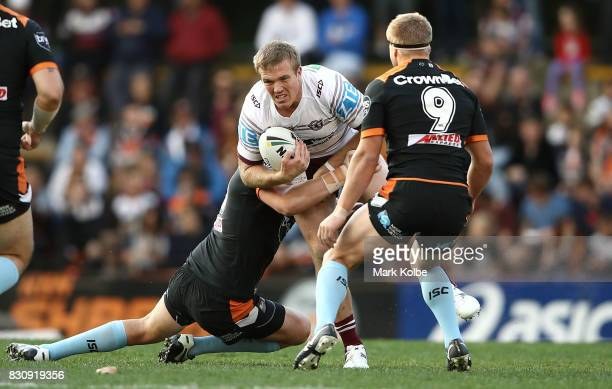 Jake Trbojevic of the Sea Eagles is tackled during the round 23 NRL match between the Wests Tigers and the Manly Sea Eagles at Leichhardt Oval on...
