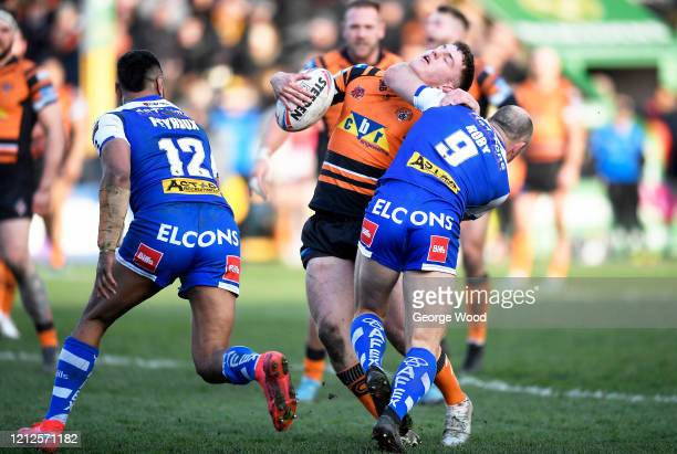 Jake Trueman of Castleford is tackled by James Roby of St Helens during the Betfred Super League match between Castleford Tigers and St Helens at The...