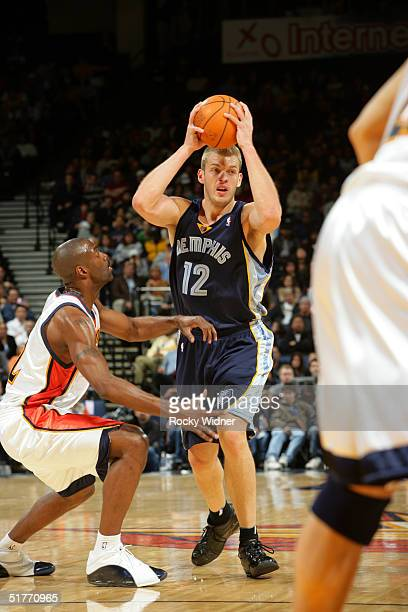 Jake Tsakalidis of the Memphis Grizzlies passes over Speedy Claxton of the Golden State Warriors at the Arena in Oakland on November 20 2004 in...