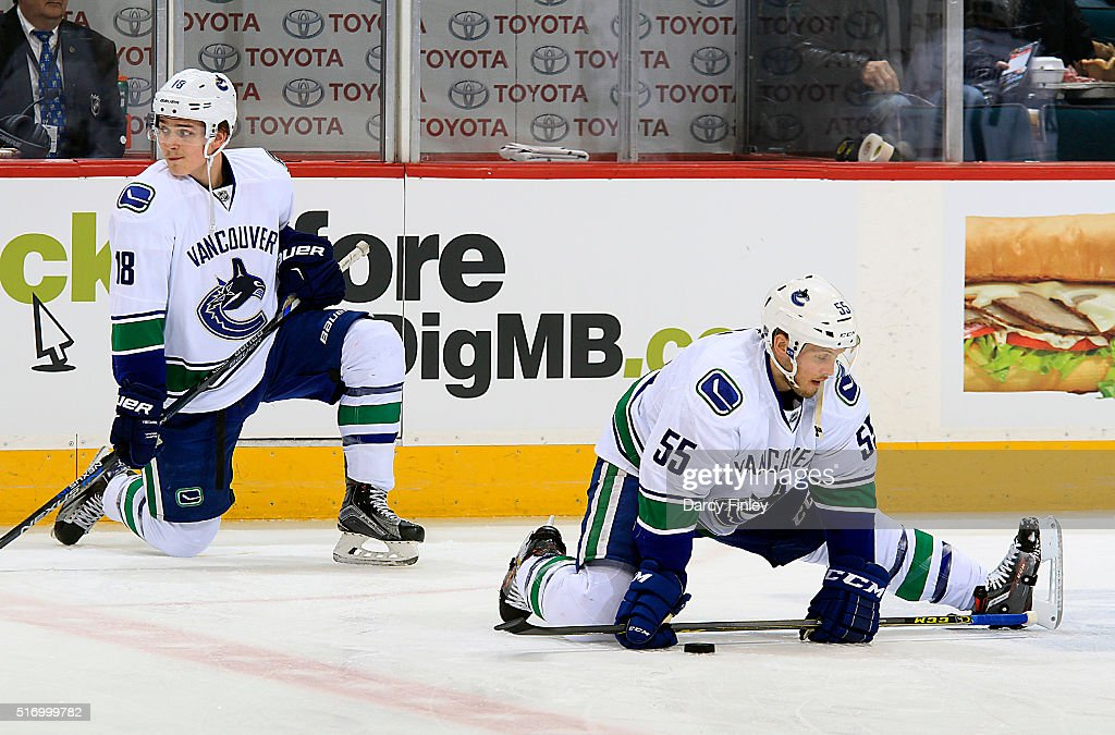 Jake Virtanen #18 and Alex Biega #55 of the Vancouver Canucks takes part in the pre-game warm up prior to NHL action against the Winnipeg Jets at the MTS Centre on March 22, 2016 in Winnipeg, Manitoba, Canada.